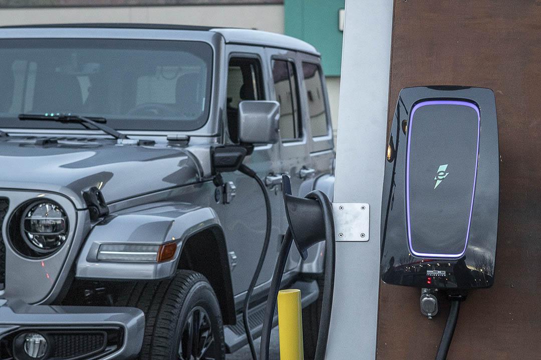 vue partielle avant du Jeep Wrangler 4xe 2021 à une borne de recharge